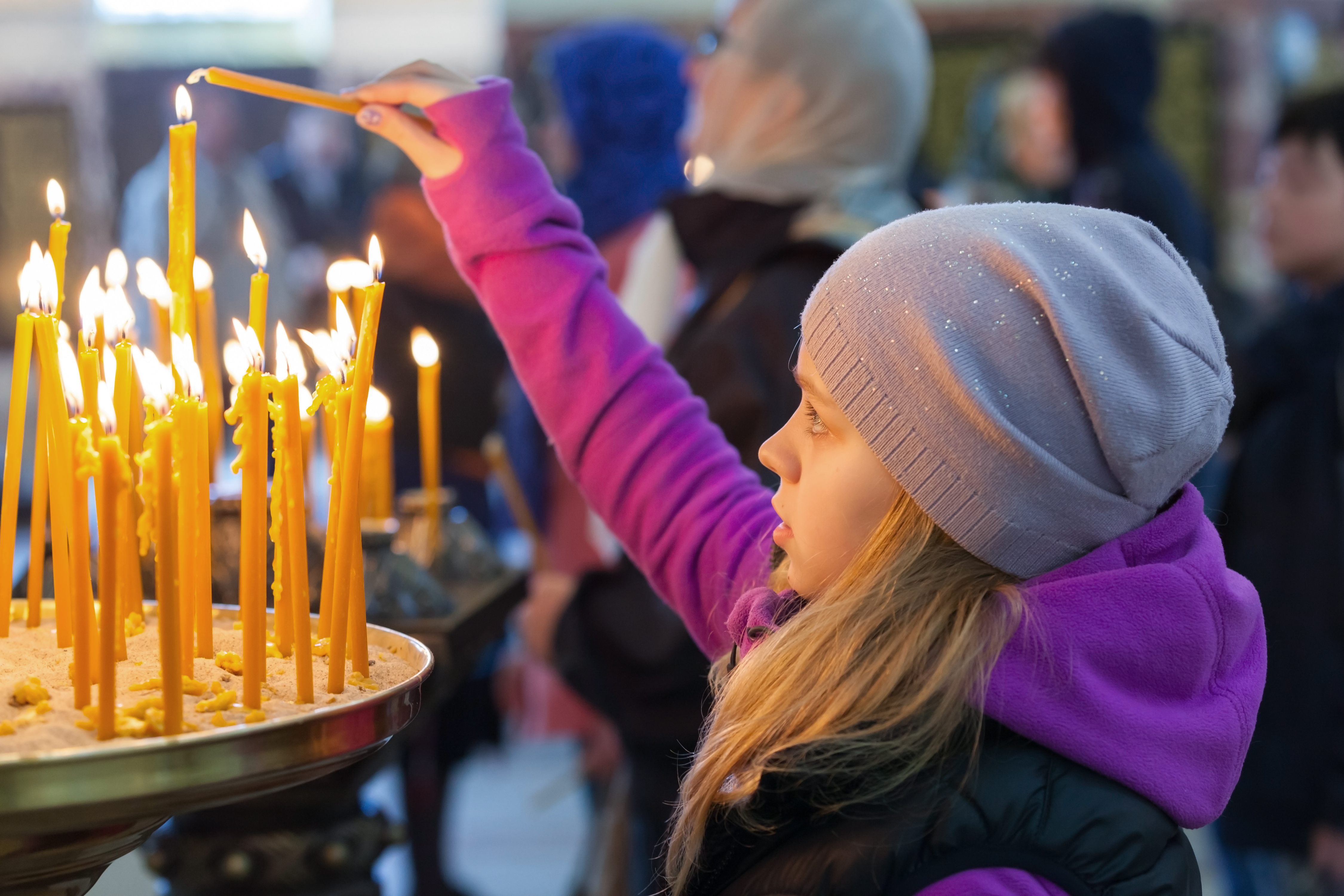 Little blond girl with candles in Orthodox Church